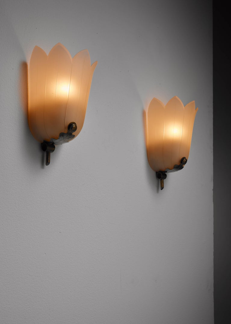 A pair of Swedish Art Deco wall lamps, made of brass and frosted glass in the shape of a flower.
