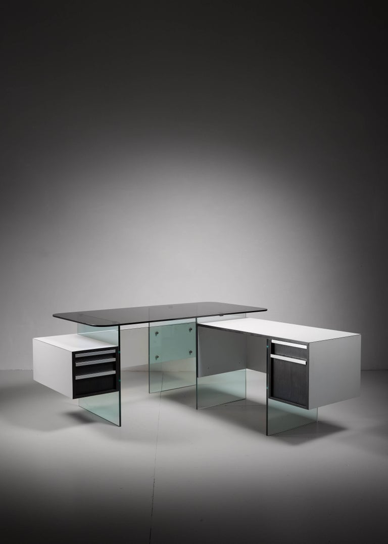 A very rare and architectural desk by French designer Xavier Marbeau. The desk can be placed in an elongated or L-shaped position. The frame and top are made of thick glass plates and the drawers are made of ebonized oak with aluminium grips. The