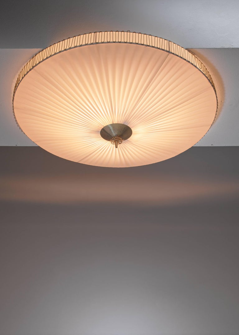 A large (75 cm diameter) round pleated flush mount ceiling lamp with a brass centre by Idman. The lamp has three light bulbs inside and is marked.  *This piece is curated for you by Bloomberry *