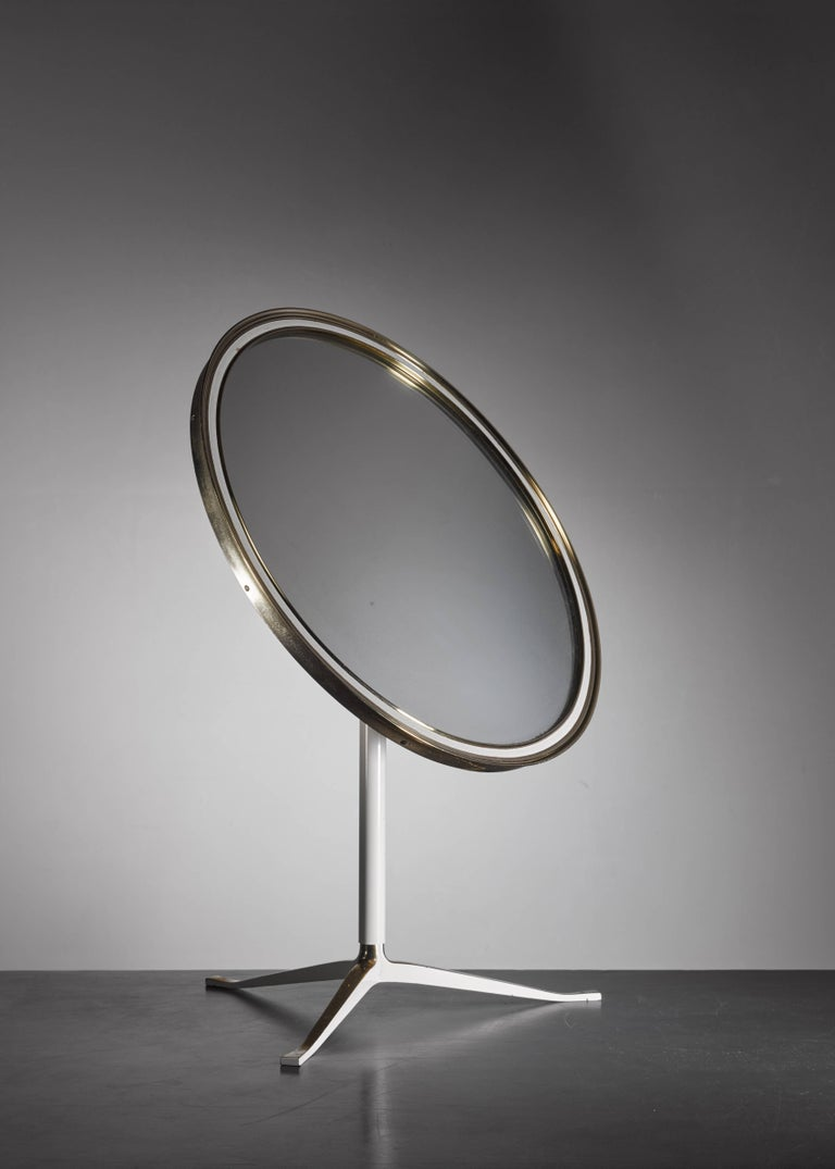 An elegant 1950s brass table mirror on a tripod foot. The stem and parts of the foot are lacquered white and the frame has a white strip inside. The back of the mirror has the original fabric cover. In a great vintage condition.