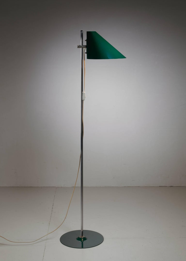 A model G185 Harlekin floor lamp by Hans-Agne Jakobsson. The lamp has a height-adjustable, dark green lacquered metal hood and foot and a metal stem. Labeled by Jakobsson and in an excellent condition.  *This piece is curated for you by Bloomberry