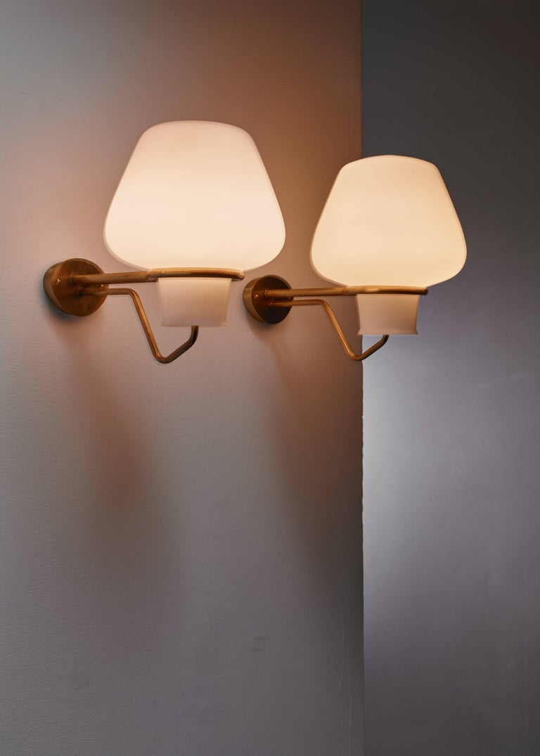 A pair of elegant Swedish wall lamps from the 1950s. From the oval brass wall mount two arms extend that hold both the light bulb and the large opaline glass diffuser. These lamps were designed by Swedish architect Gunnar Asplund and are in an
