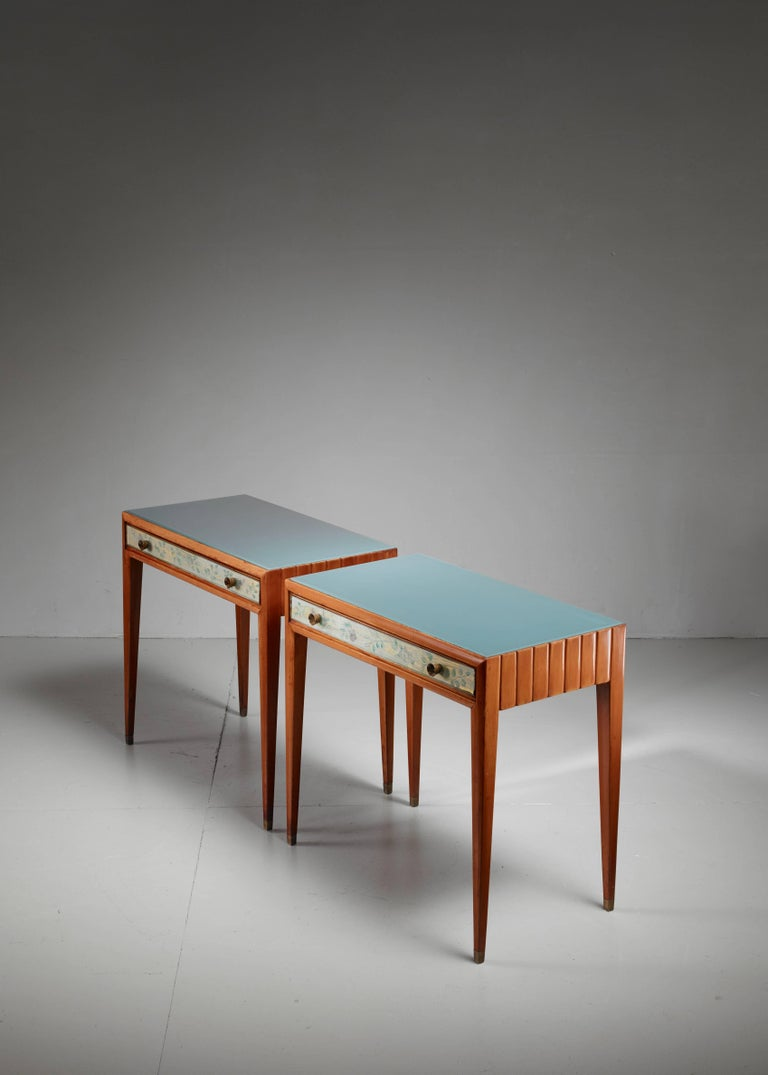 A unique pair of end tables by Osvaldo Borsani. They are made of fruitwood with reverse painted glass at the front of the drawers. The drawers have elegant bronze pulls. The paintings of the floral motifs are attributed to Adriano Spilimbergo, an