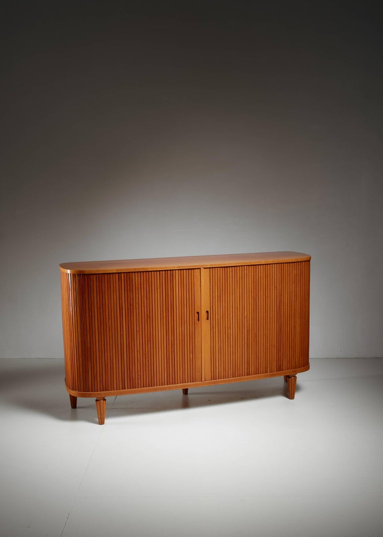 An elegant Swedish sideboard made of elm, with two tambour doors, standing on five sculpted, tapering legs. Inside the sideboard has shelves and five small document drawers. The edges underneath and above the door have been subtly decorated with