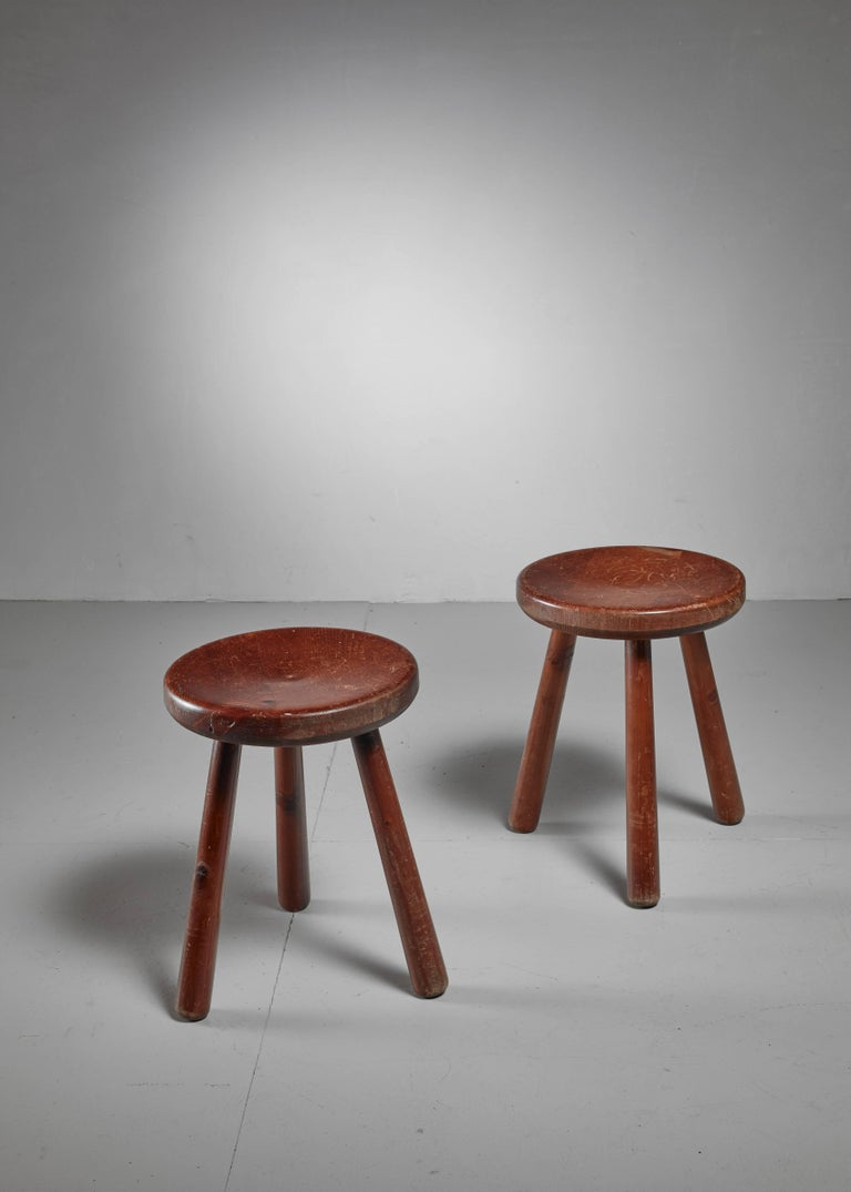 A pair of French Campagne style tripod stools, in the manner of Charlotte Perriand. They have a round (35 cm diameter) and slightly concave seating.