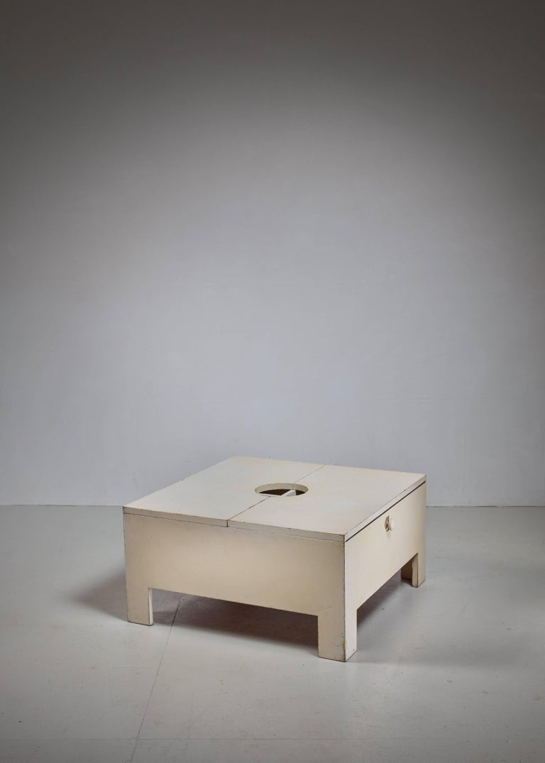 A white, wooden bar or table with a top that can be opened to reach the storage space, including a glass holder. According to markings underneath, it is a prototype from 1966, made in Brianza, Italy.