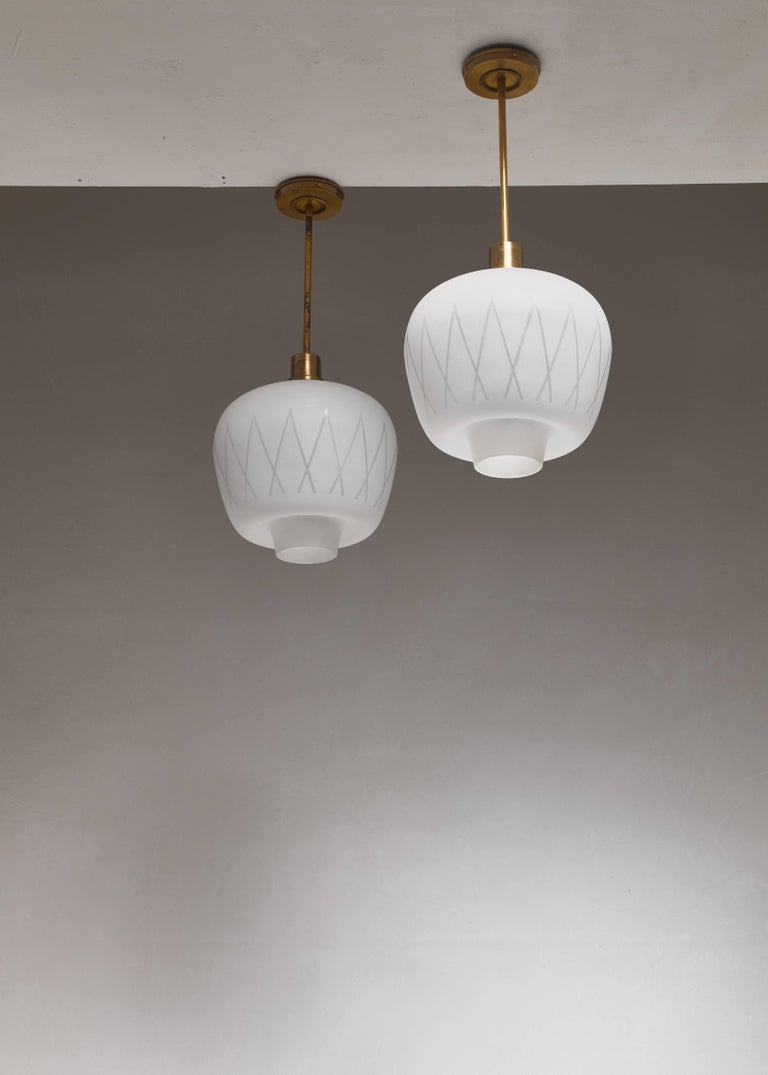 A pair of Swedish midcentury pendant lamps, made of a frosted glass shade with a geometric pattern, hanging from a brass mount. The design is reminiscent of the lamps by Hans Bergström for Lyktan.  The height of the shades is 25 cm. The total drop