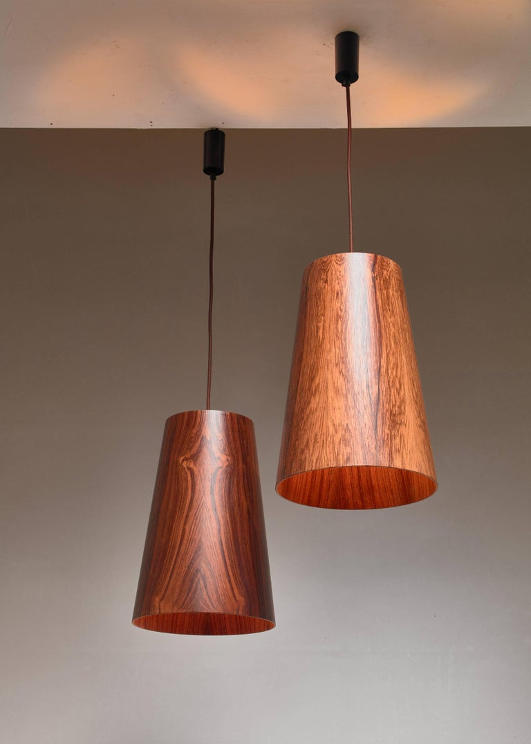 A pair of 1960s wooden pendant lamps, attributed to Östen & Uno Kristiansson for Luxus, Vittsjö, Sweden. The lamps are made of large (40.5 cm/16