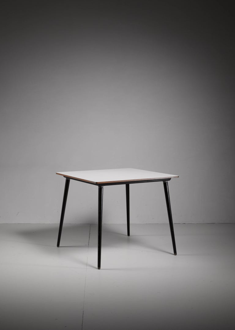 A small wooden model DTW-40 table, designed by Charles Eames for Herman Miller. It has a white laminated top with wonderful deep dark blue dowel legs. The legs can be unscrewed for easy transport and storage.
