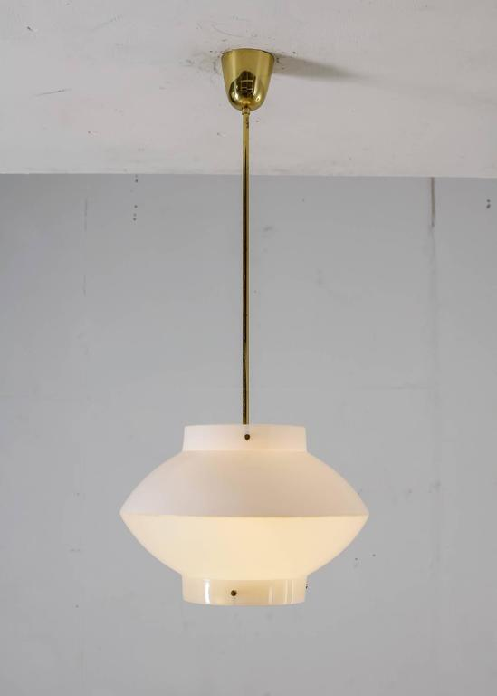 A white plexiglass model 61-380 pendant by Yki Nummi for Orno, Finland. The lamp has a brass ceiling mount and stem and a brass ring underneath. The total height of the lamp is 89 cm (35 inch) and the shade is 27.5 cm (11 inch) high. A beautiful and