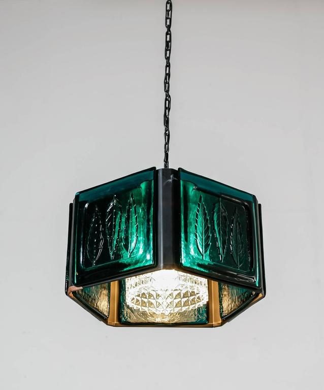 A pentagonal pendant by Erik Höglund for Kosta Boda, Sweden. The lamp is made of a metal frame with five plates of  blue textured glass inserted. Inside is a textured clear glass diffuser. It hangs from a metal chain.  In a very  good vintage