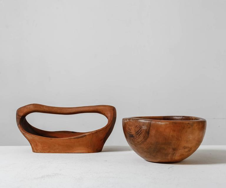 A pair of handcrafted wooden bowls from France. One has a free-form rectangular shape with a handle and the other is round.  The measurements stated are of the long bowl. The round bowl is 12.5 cm (5 inch) high and has a diameter of 24.5 cm (9.5