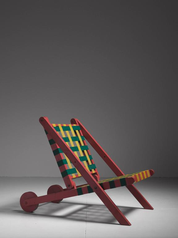 A folding lounge chair, made of a red painted pine frame with a backrest and seating made of green and yellow parachute webbing. The back legs have wheels attached to them.  This chair was based on a build-it-yourself pattern from 1952. With this