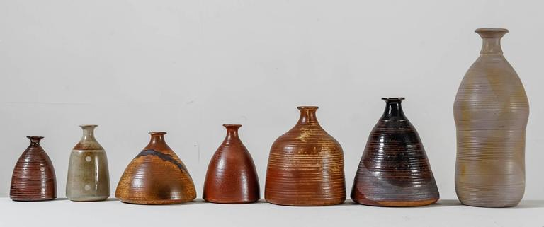 A collection of seven vases by French ceramist Franco Agnese. The vases have an earth tone finish and are all marked by Agnese and in a great, never used, condition.  The smallest piece of this collection has a diameter of 10.5 cm (4