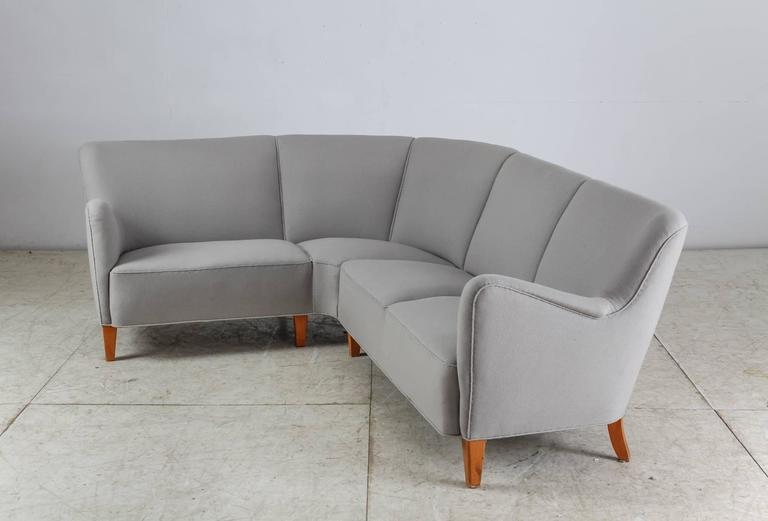 A large Danish corner sofa standing on eight stained beech legs and upholstered with a light grey wool. The sofa can be easily disassembled into two parts. The wool has age-related wear and it can be professionally reupholstered in our in-house