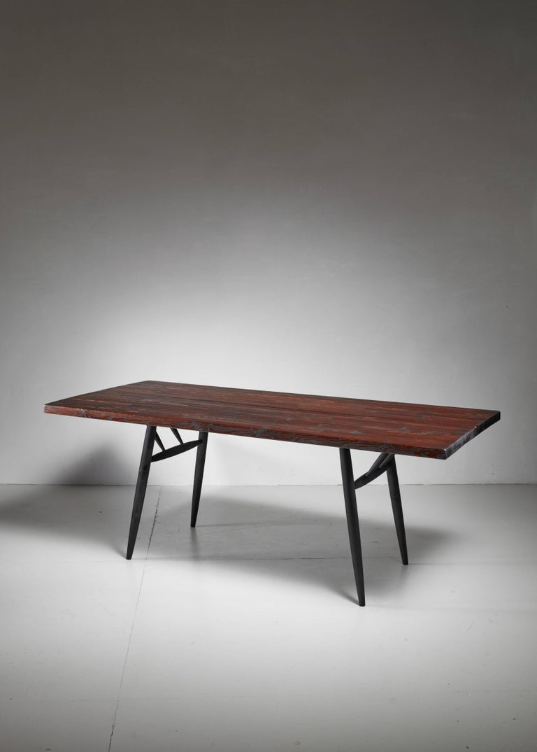 A stained pine dining table by Ilmari Tapiovaara for Laukaan Puu. Marked by Laukaan Puu and in a very good condition.