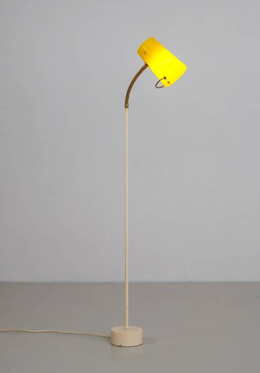 "A Mid-Century Scandinavian floor lamp, made of a white lacquered metal base and stem with a flexible brass part, making the hoofd fully adjustable. The hood (12.5 cm/5"" diameter) is made of cylindrical, tapering yellow plexiglass with a brass"