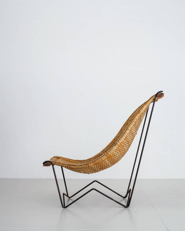A 'Duyan' lounge chair by John Risley, made of a thin iron frame with a woven rattan sling seating. The hammock-like seating is fixed with two teak slats. A beautiful chair combining Mid-Century American design and craftsmanship. Both a sculptural