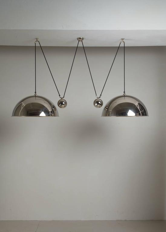 A Florian Schulz double 'Posa' pendant lamp with two shades and two counterweights. The lamps are made of nickel-plated brass.