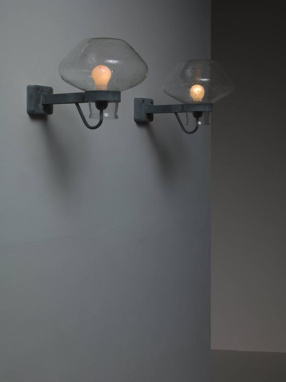 A pair of Mid-Century Swedish wall lamps by Gunnar Asplund for ASEA. From the wall mount two grey-blue metal arms extend that hold both the light bulb and the large clear glass diffuser.  * This piece is offered to you by Bloomberry, Amsterdam *