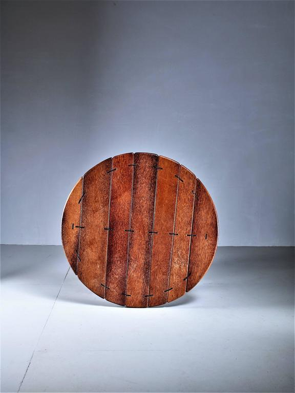 A large and round studio crafted coffee table in palmwood, from Australia The table has a steel frame and the wood parts are connected with rope and leather.