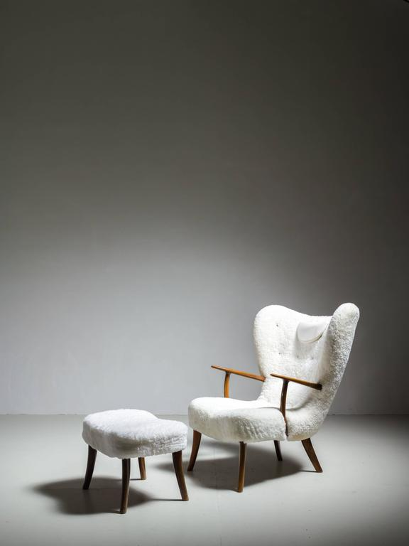A high and wide wingback oak lounge chair and matching ottoman, with a new white sheepskin upholstery. These items were designed by Acton Schubell and Ib Madsen, circa 1950.  * This piece is offered to you by Bloomberry, Amsterdam *  The