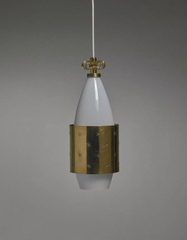 A rare model K2-12 pendant by Paavo Tynell for Idman. The lamp is made of an opaline glass diffuser and a brass shade and crown. The shade has star-shaped perforations.  * This piece is offered to you by Bloomberry, Amsterdam *