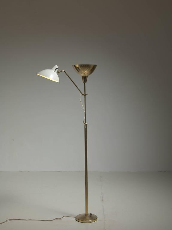 A stunning floor lamp with two shades, one brass uplighter and a height-adjustable shade of white lacquered metal. The brass shade has pin point perforations for a beautiful light distribution.  The design of the lamp is reminiscent of the work of
