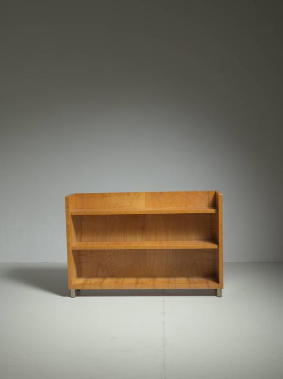 A model 'Birka' bookcase by Axel Einar Hjorth for Nordiska, Sweden. The bookcase is made of olive ash and maple, standing on round metal feet. This piece is labeled by Nordiska with the serial code 'R 38667 C'. This code indicates it was made in