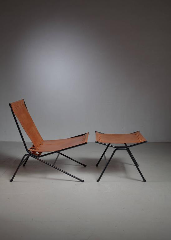 An Allan Gould 'bow'' lounge chair with a matching ottoman. The pieces are made of a black iron frame with a natural leather sling seating. They are professionally reupholstered in our in-house atelier. * This piece is offered to you by Bloomberry,