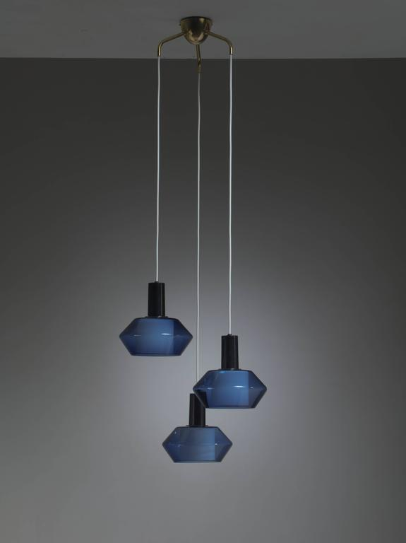 Chandelier of three diamond shaped K2-140 lamps, designed by Tapio Wirkkala and produced by Iittala on a brass three armed ceiling mount. They are original old stock from the 1950s, with labels and in perfect condition.   Each lamp hold an opaline