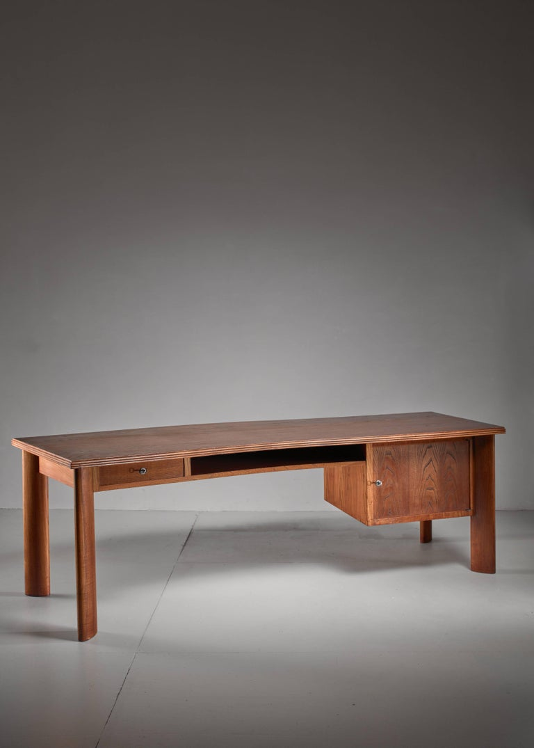 A large teak desk by Bela Angelus. The Hungarian born but Milan based architect who worked between the 1930s and 1960s. The desk has a small drawer and storage space on the left and a larger storage with drawer on the right.