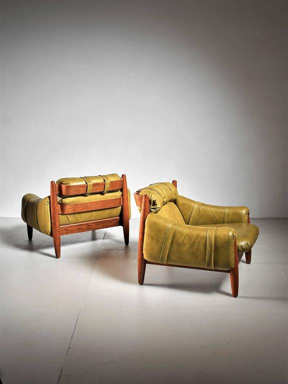 A pair of Brazilian lounge chairs in the manner of Percival Lafer. They are made of oak with green leather cushions. * This set is offered to you by Bloomberry, Amsterdam *