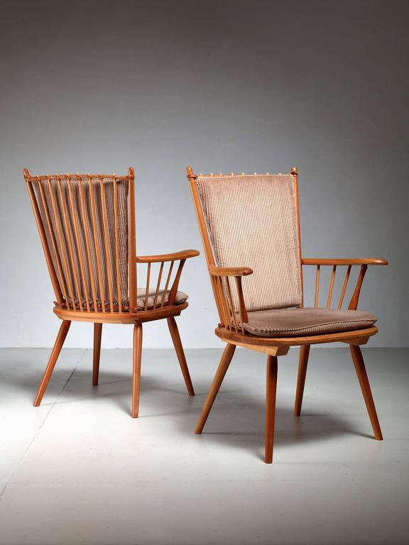 A pair of cherrywood arts and crafts chairs by Albert Haberer for Hermann Fleiner, Stuttgart, circa 1950. The chairs have loose taupe fabric cushions. The flexible backrest is made of thin spindles, held together with a leather connection. The