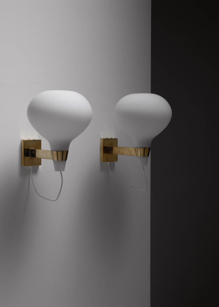 A pair of very rare wall lamps by Lisa-Johansson Pape for Orno. The lamps are are made of a brass wall mount, holding an opaline glass shade.