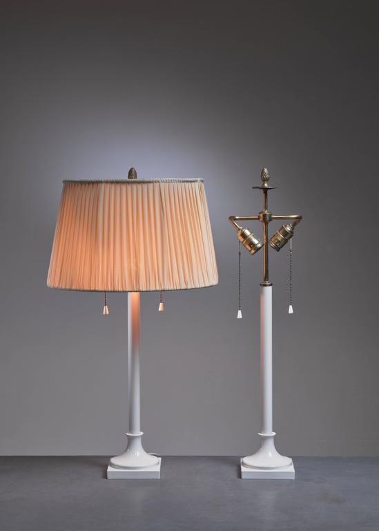 A pair of white porcelain table lamps, designed by Alice von Pechmann for KPM Berlin. The lamp has two fittings and a brass pinecone decoration on top.  The measurements, price and shipment costs stated are of the bases without a shade.  * This