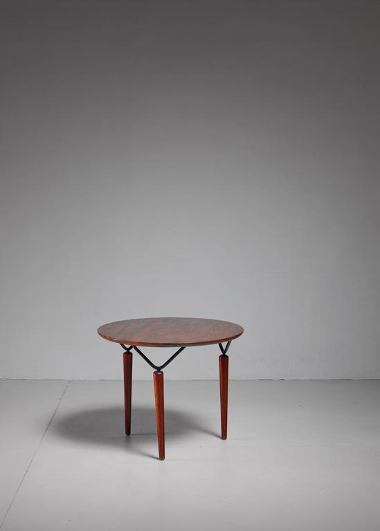 A beautiful round coffee or side table by Allen Gould. The table is made of a metal frame with tapering walnut feet and top.