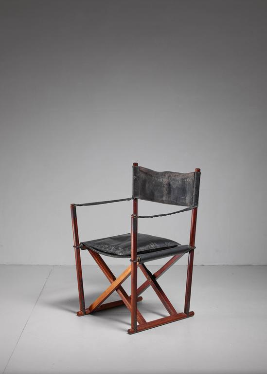 A foldable safari chair by Danish architect and designer Mogens Koch in rosewood. This chair was originally designed in 1932, but wasn't fully taken into production until 1960, by Interna as the MK-16 chair. The chair is made of a stained beech