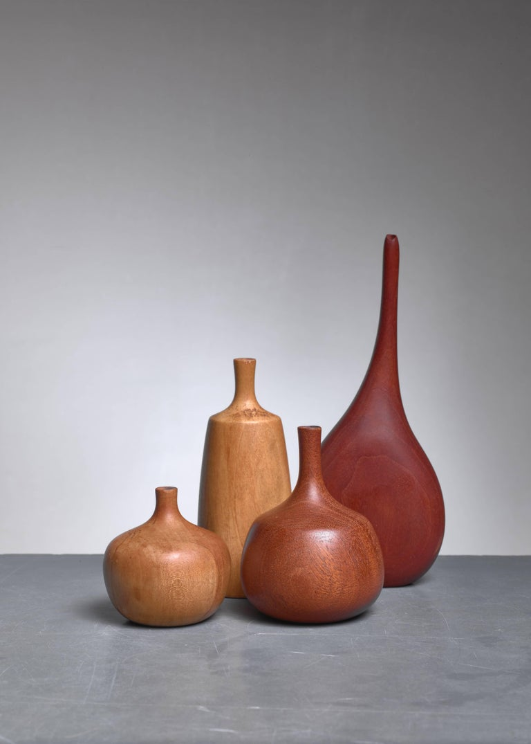 A set of four small vase made of turned wood, three of them by the be known American Craftsman woodturner Rude Osolnik.  The three smaller pieces by Osolnik are made of maple, mahogany and poplar. The largest, walnut, vase is made by an unidentified