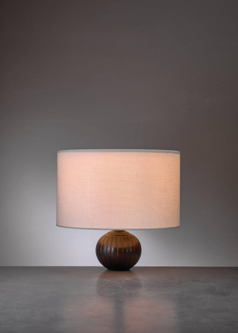 A bulbous table lamp by Danish designer Ib Just Andersen (1884-1943). The lamp is made of Disko metal; an alloy of lead and antimony, which was Andersen's own invention and named after the Disko Bay of Greenland, where he grew up. Signed with