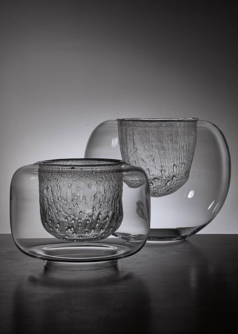 A pair of glass bowls by Timo Sarpaneva for Iittala, Finland. Smooth glass on the outside and ice glass on the inside. These pieces are original Finn Form stock from the 1960s and never used, with labels and in perfect condition. Marked by Sarpaneva