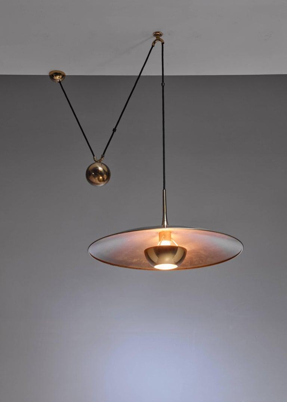A brass model 'Onos 55' pendant lamp with a heavy brass counterweight, by German designer Florian Schulz.