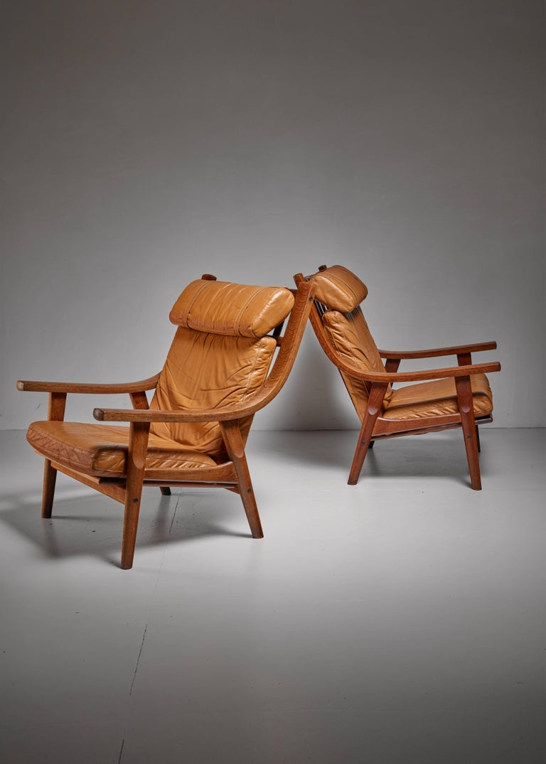 A pair of model GE-530 lounge chairs by Hans Wegner for GETAMA. The chairs are made of a stained oak frame with curved armrests and loose brown leather cushions. A very inviting pair of chairs. They have a wonderful mild wear, the later is softened