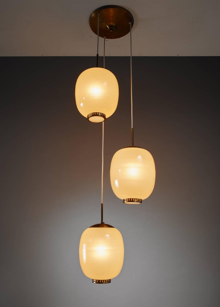 A chandelier with three pendant lamps by Danish designer Bent Karlby. The lamps are made of yellow glass with a striped pattern and hang from a brass canopy. The lamps have a brass ring with a frosted glass diffuser underneath.