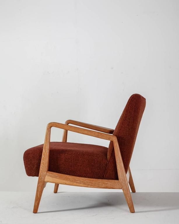 A comfortable lounge chair by Jens Risom with a walnut frame and integrated cushions with a red-brown wool upholstery. Labeled by Jens Risom Design Inc. and in a great condition with minor wear to the wool. * This is piece is offered to you by