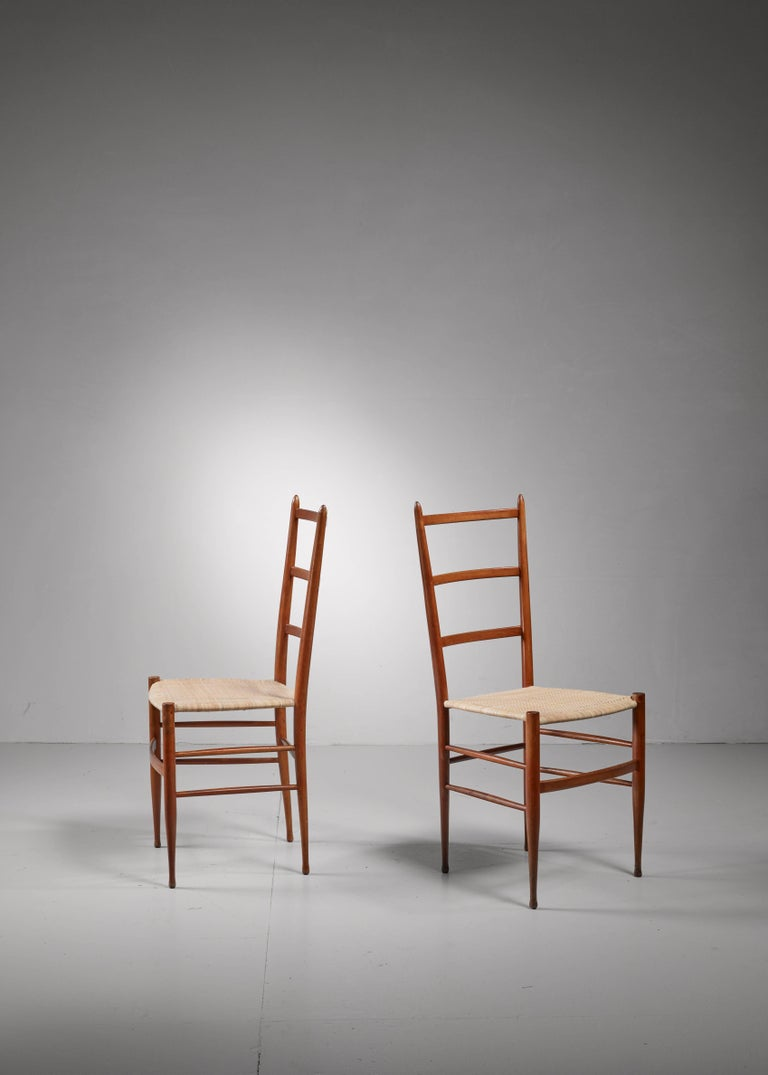 A pair of wooden Chiavari chairs with a woven cane seating.The chairs have been professionally reupholstered.  The slim and light chairs from Chiavari date back to 1807 and were the inspiration for Gio Ponti's 'superleggera' chair.