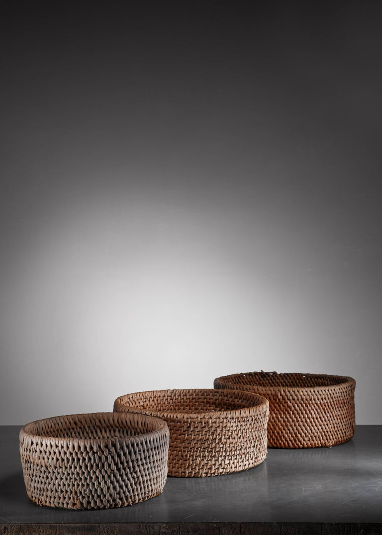 A set of three round Folk Art baskets, made of woven twigs and birch bark.