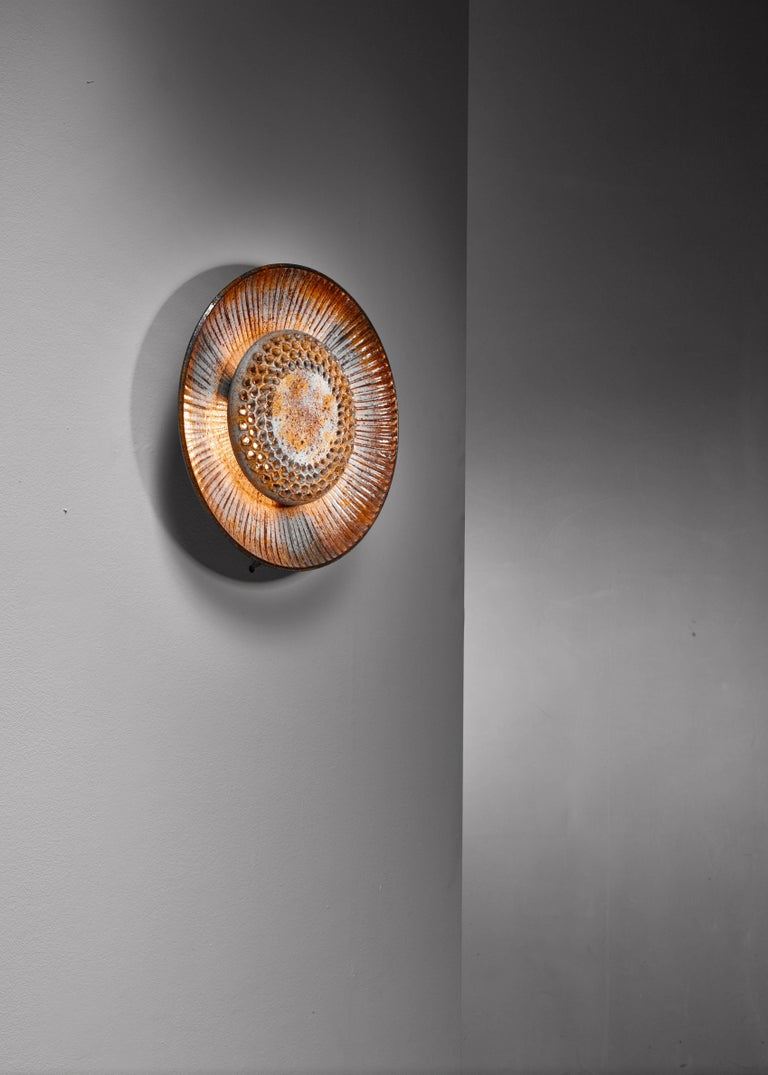 A ceramic wall lamp by Løvemose in a wonderful color combination. The earth tones combined with the grey blue gives it a cool warmth and when lit it is like a beautiful evening sky.