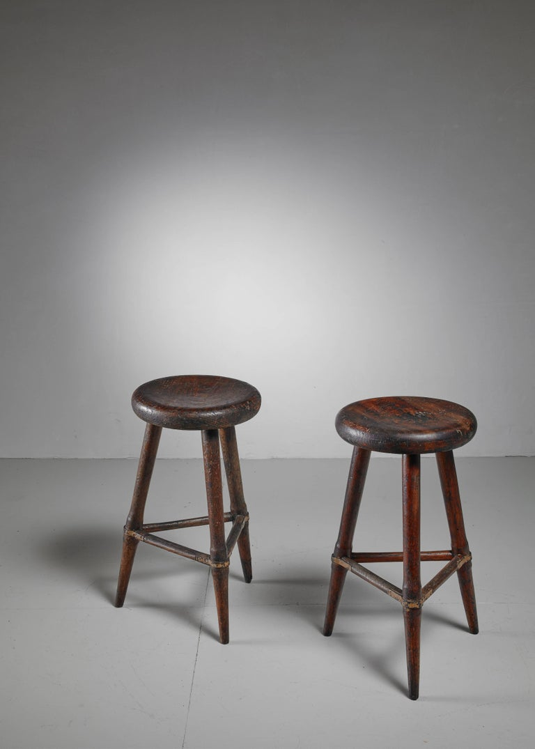 A pair of high Scandinavian wooden tripod stools. The iron in combination with the heavy patina of the wood gives these pieces a beautiful, rugged look. The three legs are held together with wooden dowels with wonderful iron connections.  *This set