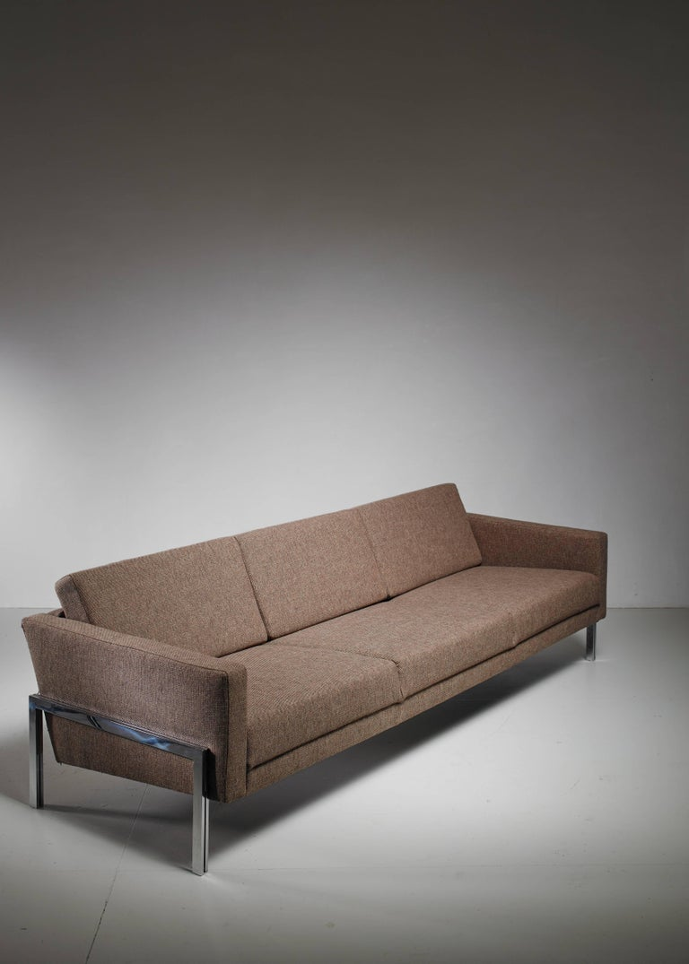 A three-seat sofa by Swiss designer Kurt Thut. The sofa has a metal frame and is newly upholstered in brown grey fabric and in a perfect condition.  We have a matching pair of lounge chairs available.     *This piece is curated for you by Bloomberry